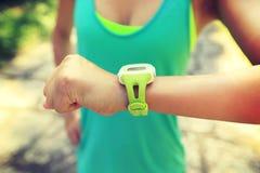 Γυναίκα jogger έτοιμη να τρέξει το σύνολο και την εξέταση το αθλητικό έξυπνο ρολόι Στοκ Εικόνες