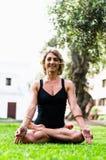 Γυναίκα Meditating και γιόγκα άσκησης, Padmasana Περισυλλογή την ηλιόλουστη ημέρα φθινοπώρου στο πάρκο υπαίθριο workout στοκ φωτογραφίες