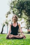 Γυναίκα Meditating και γιόγκα άσκησης, Padmasana Περισυλλογή την ηλιόλουστη ημέρα φθινοπώρου στο πάρκο υπαίθριο workout στοκ φωτογραφία
