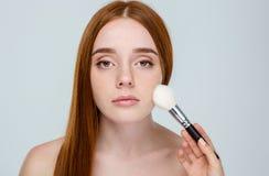 Γυναίκα Redhair που χρησιμοποιεί makeup τη βούρτσα στοκ εικόνες
