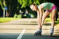 Γυναίκα Rollerblading Το νέο ελκυστικό θηλυκό πρότυπο ικανότητας είναι εκτάριο στοκ εικόνα