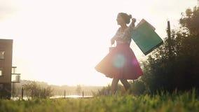 Γυναίκα Shopaholic στην όμορφη περιστροφή φορεμάτων γύρω από το κράτημα πολλών τσαντών αγορών περπατώντας στην οδό μέσω του ήλιου απόθεμα βίντεο