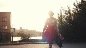 Γυναίκα Shopaholic στο όμορφο φόρεμα που κρατά πολλές τσάντες αγορών περπατώντας στην οδό μέσω του ήλιου κατά τη διάρκεια του ηλι φιλμ μικρού μήκους