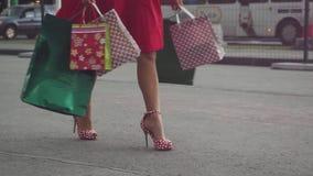 Γυναίκα Shopaholic στο όμορφο φόρεμα που κρατά πολλές τσάντες αγορών περπατώντας στην οδό σε σε αργή κίνηση 1920x1080 απόθεμα βίντεο