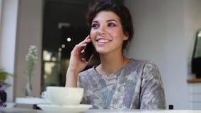 Γυναίκα Smartphone που μιλά στο τηλέφωνο καθμένος στον καφέ με ένα φλιτζάνι του καφέ στον πίνακα Χαμογελά και γελά απόθεμα βίντεο