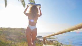 Γυναίκα Surfer στη μετάβαση ταξιδιού διακοπών παραλιών που κάνει σερφ το περπάτημα με την ιστιοσανίδα στο ηλιοβασίλεμα στην τροπι απόθεμα βίντεο