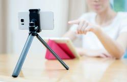 Γυναίκα vlogger που κοιτάζει χρησιμοποιώντας ipad τον υπολογιστή και τη μαγνητοσκόπηση στο τηλεοπτικό χ στοκ φωτογραφίες με δικαίωμα ελεύθερης χρήσης