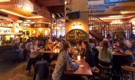 Γυναίκες ανδρών amd που έχουν το γεύμα και που πίνουν την μπύρα στο φραγμό με τα εκλεκτής ποιότητας έπιπλα και τις διακοσμήσεις Στοκ Εικόνες