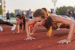 Γυναίκες ικανότητας αθλητών ώθηση-UPS που ασκούν στο στάδιο υπαίθρια εκπαιδευτικός Στοκ Φωτογραφία