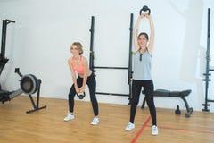 Γυναίκες ικανότητας που εργάζονται με το κουδούνι κατσαρολών στη γυμναστική Στοκ Εικόνες