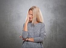 Γυναίκες με ένα λυπημένο πρόσωπο σε μια γκρίζα ανασκόπηση Στοκ φωτογραφία με δικαίωμα ελεύθερης χρήσης