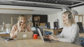 Γυναίκες με τα ακουστικά με τις συζητήσεις μικροφώνων πελάτες μέσω του υπολογιστή Οι γυναίκες δακτυλογραφούν στους υπολογιστές απόθεμα βίντεο