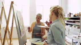 Γυναίκες με τις βούρτσες που χρωματίζουν στο σχολείο τέχνης απόθεμα βίντεο