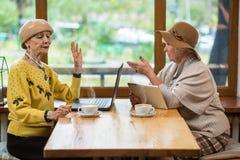 Γυναίκες με τις συσκευές στον καφέ στοκ φωτογραφίες
