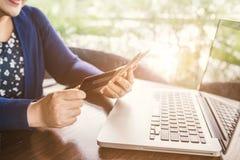 Γυναίκες με το κινητό τηλέφωνο και την πληρωμή με πιστωτική κάρτα Στοκ Εικόνες