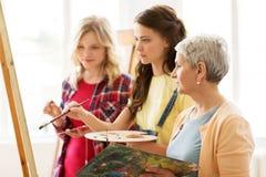 Γυναίκες με easel και παλέτες στο σχολείο τέχνης Στοκ φωτογραφίες με δικαίωμα ελεύθερης χρήσης