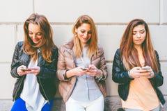 Γυναίκες που δακτυλογραφούν στα κινητά τηλέφωνα Στοκ Φωτογραφία
