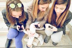 Γυναίκες που δακτυλογραφούν στα κινητά τηλέφωνα Στοκ φωτογραφία με δικαίωμα ελεύθερης χρήσης