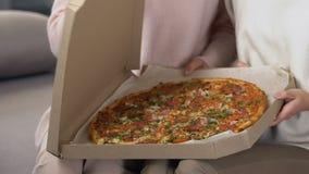 Γυναίκες που ανοίγουν το κουτί από χαρτόνι με τη φρέσκια αρωματική πίτσα, υπηρεσία παράδοσης τροφίμων απόθεμα βίντεο