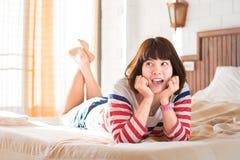 Γυναίκες που βρίσκονται στο κρεβάτι με το πρόσωπο χαμόγελου Στοκ φωτογραφία με δικαίωμα ελεύθερης χρήσης