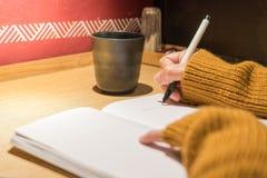 Γυναίκες που γράφουν ένα βιβλίο στον ξύλινο πίνακα, κενό βιβλίο για το διάστημα αντιγράφων, έννοια εκπαίδευσης Στοκ Εικόνες