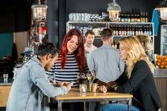 Γυναίκες που εξετάζουν το φίλο που χρησιμοποιεί το κινητό τηλέφωνο στο φραγμό Στοκ Φωτογραφίες