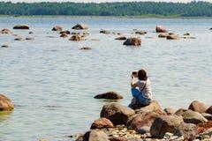 Γυναίκες που κάθονται στην πέτρα κοντά στη θάλασσα και που παίρνουν τη φωτογραφία από την τηλεφωνική κάμερα Stone και τοπίο θάλασ Στοκ φωτογραφία με δικαίωμα ελεύθερης χρήσης