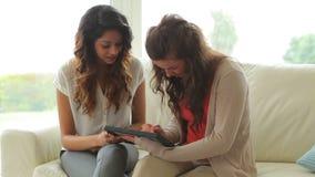 Γυναίκες που κάθονται στον καναπέ που κρατά ένα PC ταμπλετών απόθεμα βίντεο