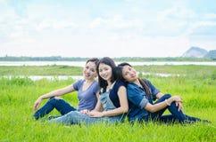 Γυναίκες που κάθονται στο λιβάδι και το χαμόγελο Στοκ Εικόνες