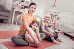 Γυναίκες που κάνουν την κατάρτιση γιόγκας για τα παιδιά στο σπίτι στοκ φωτογραφίες