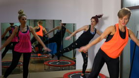 Γυναίκες που κάνουν τη σύνοδο ικανότητας με το τραμπολίνο στη γυμναστική απόθεμα βίντεο