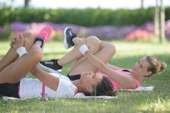 Γυναίκες που κάνουν τις ασκήσεις ποδιών που τοποθετούνται στη χλόη στοκ φωτογραφίες