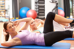 Γυναίκες που κάνουν τις τεντώνοντας ασκήσεις στη γυμναστική στοκ φωτογραφία με δικαίωμα ελεύθερης χρήσης
