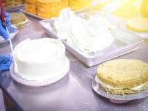 Γυναίκες που κατασκευάζουν το κέικ στη βιομηχανία κέικ με τη θαμπάδα κινήσεων Στοκ Εικόνα