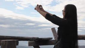 Γυναίκες που πυροβολούν τη φωτογραφία ή selfie με το smartphone ή κινητός στο υπόβαθρο του μπλε ουρανού και του σύννεφου φιλμ μικρού μήκους