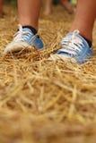 Γυναίκες που φορούν τα μπλε παπούτσια που στέκονται στο άχυρο ρυζιού Στοκ Φωτογραφία