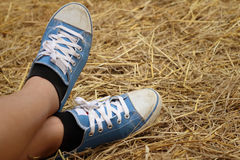 Γυναίκες που φορούν τα μπλε παπούτσια που στέκονται στο άχυρο ρυζιού Στοκ Εικόνες