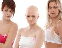 Γυναίκες που φορούν την κορδέλλα Awereness καρκίνου του μαστού στοκ φωτογραφίες