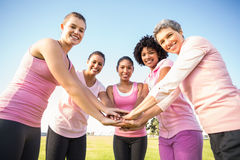 Γυναίκες που φορούν το ροζ για το καρκίνο του μαστού και που βάζουν τα χέρια από κοινού Στοκ Φωτογραφία