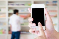 Γυναίκες που χρησιμοποιούν το έξυπνο τηλέφωνο στο φαρμακείο στοκ εικόνες