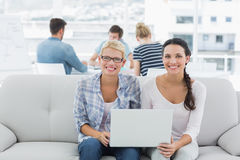 Γυναίκες που χρησιμοποιούν το lap-top με τους συναδέλφους στο υπόβαθρο στο δημιουργικό γραφείο Στοκ Φωτογραφίες