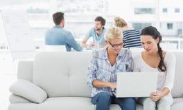 Γυναίκες που χρησιμοποιούν το lap-top με τους συναδέλφους στο υπόβαθρο στο δημιουργικό γραφείο Στοκ φωτογραφίες με δικαίωμα ελεύθερης χρήσης