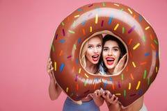 Γυναίκες σε beachwear έχοντας τη διασκέδαση με διαμορφωμένο το doughnut στρώμα καρδιών Στοκ εικόνες με δικαίωμα ελεύθερης χρήσης