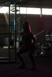 Γυναίκες σκιαγραφιών που στέκονται ισχυρές στη γυμναστική και που λυγίζουν τους μυς Στοκ Εικόνες