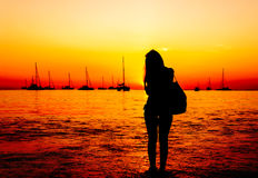 Γυναίκες σκιαγραφιών στην παραλία άμμου με το ηλιοβασίλεμα στο λυκόφως Στοκ Φωτογραφίες