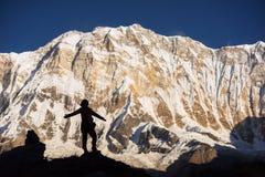 Γυναίκες σκιαγραφιών backpacker στο βράχο και το Annapurna Ι υπόβαθρο 8,091m από Annapurna Basecamp, Νεπάλ Στοκ φωτογραφίες με δικαίωμα ελεύθερης χρήσης