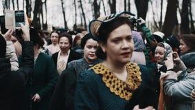 Γυναίκες στα ιστορικά κοστούμια που περπατούν trought το διάδρομο του πλήθους ανθρώπων στο πάρκο φιλμ μικρού μήκους