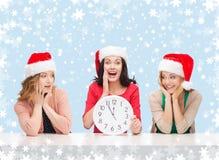 Γυναίκες στα καπέλα αρωγών santa με το ρολόι που παρουσιάζει 12 Στοκ φωτογραφίες με δικαίωμα ελεύθερης χρήσης