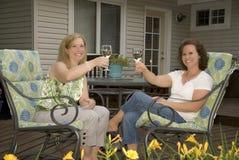 Γυναίκες στα ψήνοντας γυαλιά κρασιού Patio στοκ εικόνα με δικαίωμα ελεύθερης χρήσης