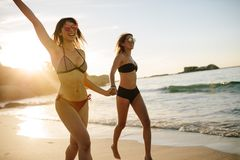 Γυναίκες στην παραλία που τρέχει και που γελά Στοκ φωτογραφία με δικαίωμα ελεύθερης χρήσης